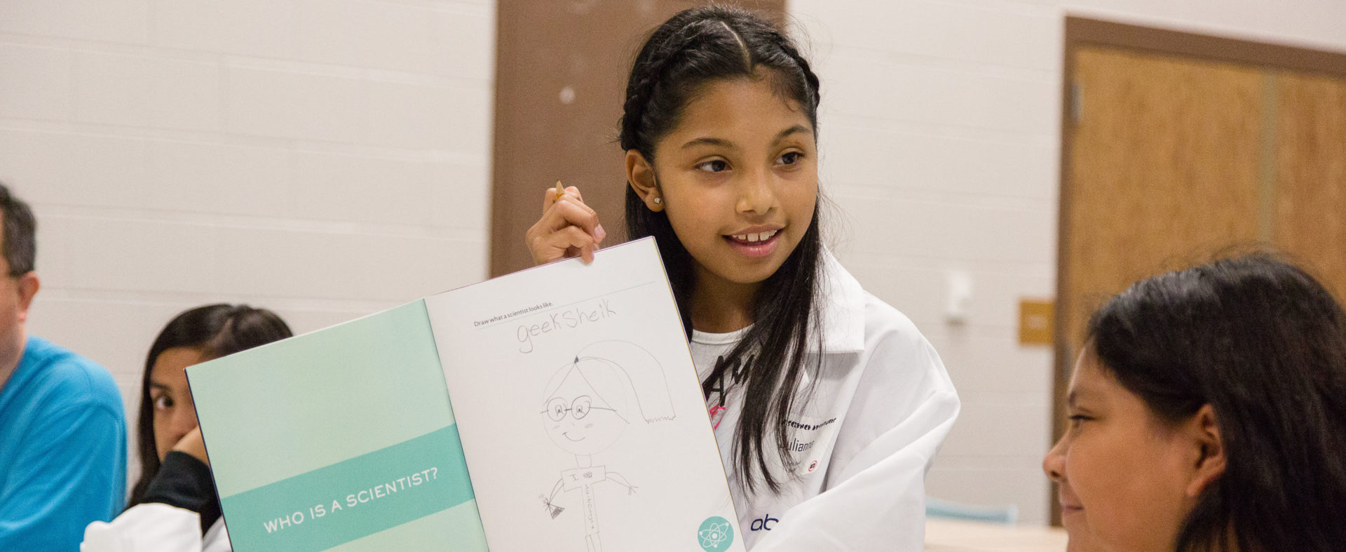 A young child in a lab coat shows off her drawing of what a scientist looks like.