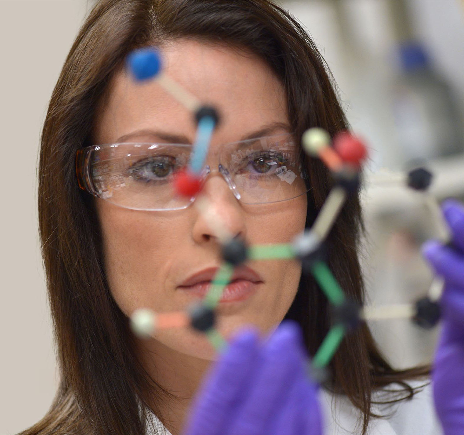 A close up female scientist wearing goggles and building a prototype.